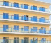 Prednja fasada Hotela Africa u Rodosu u Grčkoj. Žuta fasda, staklena ograda, prozori, vrata.