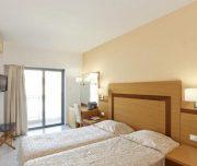 Jedna od soba Hotela Africa u Rodosu u Grčkoj. Namšteni kreveti, osunčana soba, stolica, ogledalo, sto, TV, klima