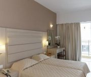 Jedna od soba Hotela Africa u Rodosu u Grčkoj. Namšteni kreveti, osunčana soba, stolica, ogledalo, sto, TV, klima, cvece, telefon.
