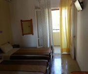 Jedna od soba vile Platania na Krfu u Grčkoj. Namešteni kreveti, TV.