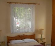 Jedna od soba vile Vasiliki na Krfu u Grčkoj. Namešten krevet, prozor, lampe.