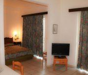 Jedna od soba u aparthotelu Royal u Rodosu u Grčkoj. Namešten krevet, TV, stolica, sto, voće.