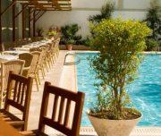Bazen hotela Best Western Plaza u Rodosu u Grčkoj. Bazen, stolice, zelenilo.