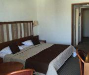 Jedna od soba hotela Best Western Plaza u Rodosu u Grčkoj. Namešten krevet, sto, stolica, TV.