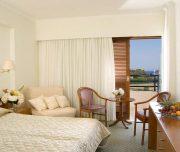 Jedna od soba hotela Best Western Plaza u Rodosu u Grčkoj. Namešten krevet, sto, stolica, terasa.