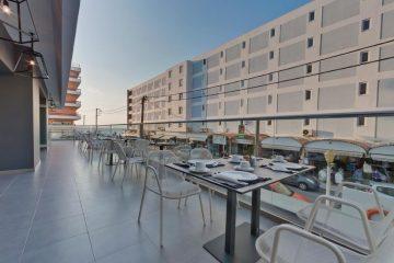 Terasa hotela Alexia Premier City u Rodosu u Grčkoj. Postavljeni stolovi, stolice, staklena ograda.