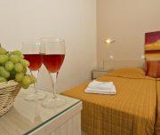Jedna od soba hotela Amaryllis u Rodosu u Grčkoj. Namešteni krevet, grožđe, vino, slike, peškiri.