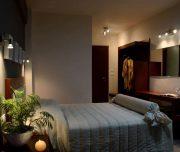 Jedna od soba hotela Amphitryon Boutique u Rodosu u Grčkoj. Namešteni kreveti, ogledalo lampe, sveće.