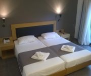 Jedna od soba hotela Butterfly Boutique u Rodosu u Grčkoj. Namešteni kreveti, lampe, peškiri, telefon.
