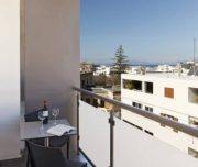 Jedna od terasa hotela Butterfly Boutique u Rodosu u Grčkoj. Stolice, sto, pogled na more, staklena ograda.