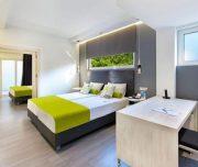 Jedna od soba Hotela Semiramis u Rodosu u Grčkoj. Namšten krevet, stolica, sto, TV.