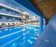 Jedan od bazena Hotela Semiramis. Bazen, ljudi, suncobrani, lezaljke.