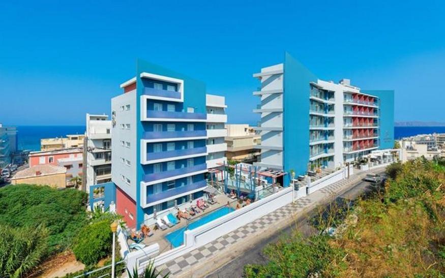 Slika spoljašnjosti hotela Semiramis. Plava fasada, bazeni, travnjak.