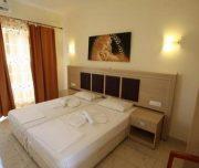 Jedna od soba hotela Grecian Fantasia Resort u Rodosu u Grčkoj. Namešteni kreveti, slika, zavesa.