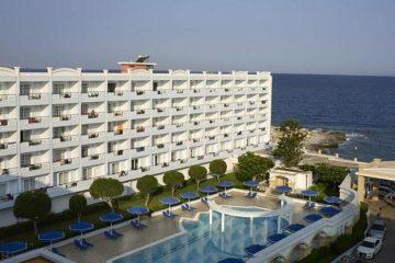 Spoljašnjost hotela Mitsis Grand u Rodosu u Grčkoj. Fasada, bazen, ležaljke, suncobrani, more.