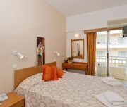 Jedna od soba hotela Vassilia u Rodosu u Grčkoj. Namešteni kreveti, peškiri, slika, sef, ogledalo, terasa, TV.