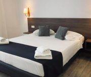 Jedna od soba hotela Virginia u Rodosu u Grčkoj. Namešten krevet, jastuci , lampa, peškiri.
