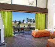 Jedna od soba hotela Virginia u Rodosu u Grčkoj. Namešten krevet, terasa, travnjak, TV.