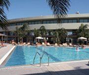 Spoljašnjost hotela Virginia u Rodosu u Grčkoj. Bazen, ljudi, ležaljke, suncobrani, hotel.